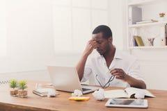 Impiegato afroamericano stanco in ufficio, lavoro con il computer portatile immagine stock libera da diritti