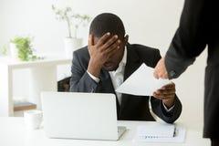Impiegato afroamericano turbato frustrato che riceve licenziamento n immagine stock libera da diritti