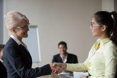 Impiegato asiatico di handshake femminile del capo che si congratula con il promo fotografie stock libere da diritti