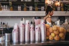 Impiegato che produce succo dentro Joe & il caffè del succo a Richmond, Londra, Regno Unito fotografia stock libera da diritti