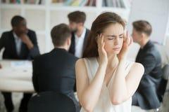 Impiegato corporativo femminile sollecitato che ha emicrania durante il briefi immagine stock