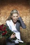 Impiegato d'uso di grido della donna dell'armamentario di spettacolo di mese contro il fondo del velluto dell'oro Fotografia Stock