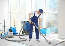 Impiegato del ` s della lavanderia a secco che rimuove sporcizia dal tappeto immagini stock