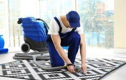 Impiegato del ` s della lavanderia a secco che rimuove sporcizia dal tappeto fotografia stock