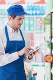 Impiegato del supermercato che lavora con una compressa fotografie stock libere da diritti