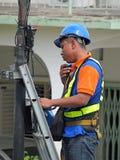 Impiegato del TM che lavora in cima al telefono palo immagini stock libere da diritti