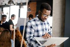 Impiegato di concetto africano che tiene il suoi computer portatile e skannig  Fotografia Stock