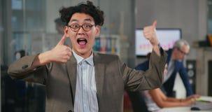 Impiegato di concetto asiatico felice che mostra i pollici di vista su stock footage