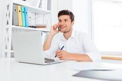 Impiegato di concetto che rivolge al telefono e che per mezzo del computer portatile Fotografia Stock Libera da Diritti