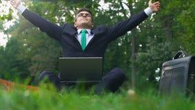 Impiegato di concetto che si siede sull'erba in parco con la respirazione del computer portatile profonda e l'allungamento archivi video