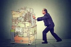 Impiegato di concetto che spinge il carretto pesante dell'aeroporto con gli zainhi e le cartelle di viaggio Fotografia Stock