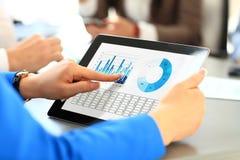 Impiegato di concetto che usando un touchpad per analizzare i dati statistici Immagine Stock
