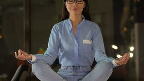 Impiegato di concetto della donna che si siede nella posizione di loto, nella riduzione di sforzo e nell'equilibrio interno stock footage