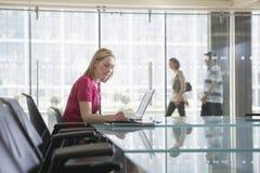 Impiegato di concetto femminile che utilizza computer portatile nell'auditorium fotografia stock