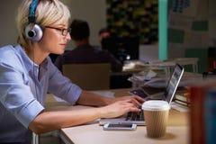 Impiegato di concetto femminile con caffè allo scrittorio che funziona tardi Fotografie Stock Libere da Diritti