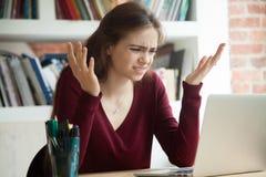 Impiegato di concetto femminile perplesso che scrolla le spalle mentre esaminando computer portatile immagini stock