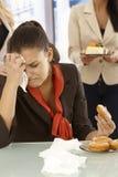 Impiegato di concetto infelice che mangia ciambella Fotografia Stock