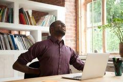 Impiegato di concetto maschio afroamericano esaurito che ha discom posteriore Fotografie Stock Libere da Diritti