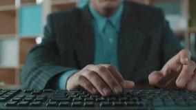 Impiegato di concetto nella battitura a macchina veloce della camicia blu del rivestimento del plaid sulla tastiera di computer video d archivio