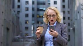 Impiegato di concetto senior che sembra emozionante leggendo lo smartphone di buone notizie, app di affari stock footage