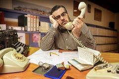 Impiegato di concetto sorpreso con il telefono a disposizione nell'ufficio in immagini stock