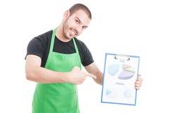 Impiegato di ipermercato che indica sulla lavagna per appunti di previsioni e di profitto Fotografia Stock Libera da Diritti