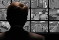 Impiegato di sorveglianza dell'uomo lavorare via il video monitor a circuito chiuso Fotografia Stock