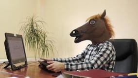 Impiegato di ufficio dello psicopatico che indossa una maschera del cavallo durante il giorno lavorativo davanti al computer video d archivio