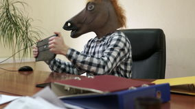 Impiegato di ufficio dello psicopatico che indossa una maschera del cavallo durante il giorno lavorativo davanti al computer archivi video