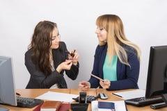 Impiegato di ufficio in una rottura per discutere i prodotti cosmetici al vostro scrittorio Immagine Stock