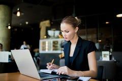 Impiegato femminile che scrive un rapporto mensile in taccuino dal NET-libro fotografia stock libera da diritti