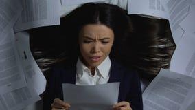 Impiegato femminile che sgualcisce documento con rabbia, odiante lavoro, concetto di burnout di lavoro video d archivio