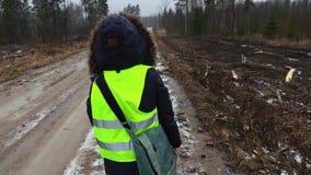 Impiegato femminile di silvicoltura che cammina e che dice nel giorno di inverno bagnato archivi video
