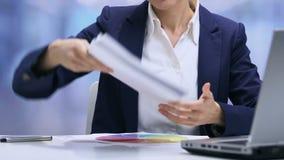 Impiegato femminile sovraccaricato che controlla i mucchi dei documenti e dei grafici, termine archivi video