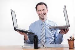 Impiegato a funzioni multiple con sorridere di 2 computer portatili Fotografia Stock Libera da Diritti