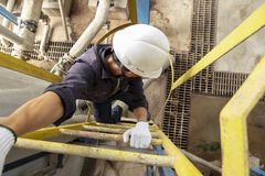 Impiegato maschio asiatico che indossa un casco di sicurezza che sale la scala fotografia stock