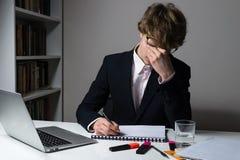 Impiegato o studente esaurito in vestito ufficiale che lavora le ore tarde allo scrittorio moderno per rispettare limite per l'as immagini stock