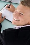 Impiegato sorridente con la penna e scheda di scrittura fotografie stock