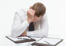 Impiegato stancato che si siede alla tavola e che piega la sua testa, sedere bianche immagine stock libera da diritti