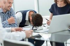 Impiegato stanco ad una riunione d'affari nell'ufficio fotografia stock