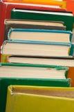 Impilamento del libro Apra i libri della libro con copertina rigida sulla tavola di legno e sul fondo blu Di nuovo al banco Copi  Fotografia Stock Libera da Diritti