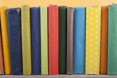 Impilamento del libro Apra i libri della libro con copertina rigida sulla tavola di legno e sul fondo giallo Di nuovo al banco Co Fotografie Stock Libere da Diritti