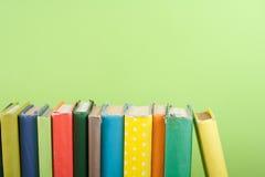 Impilamento del libro Apra i libri della libro con copertina rigida sulla tavola di legno e sul fondo verde Di nuovo al banco Cop Immagini Stock Libere da Diritti