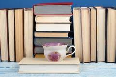 Impilamento del libro Il libro aperto, libro con copertina rigida prenota sulla tavola di legno e sul fondo blu Di nuovo al banco Fotografia Stock