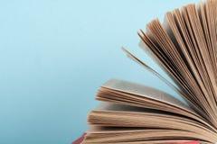 Impilamento del libro Il libro aperto, libro con copertina rigida prenota sulla tavola di legno e sul fondo blu Di nuovo al banco Fotografia Stock Libera da Diritti