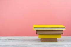 Impilamento del libro Il libro aperto, libro con copertina rigida prenota sulla tavola di legno e sul fondo blu Di nuovo al banco Immagine Stock Libera da Diritti