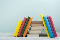 Impilamento del libro Il libro aperto, libro con copertina rigida prenota sulla tavola di legno e sul fondo blu Di nuovo al banco Immagini Stock