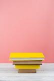 Impilamento del libro Il libro aperto, libro con copertina rigida prenota sulla tavola di legno e sul fondo blu Di nuovo al banco Immagine Stock