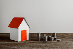 Impilamento le monete e del modello domestico per il risparmio con i soldi crescenti Fotografie Stock Libere da Diritti