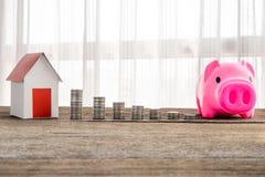 Impilamento le monete e del modello domestico per il risparmio con i soldi crescenti alla r immagine stock